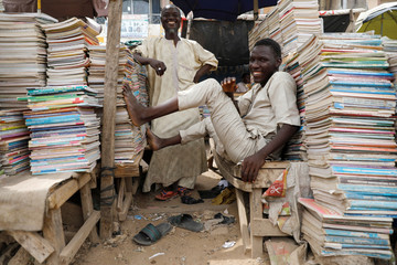 Used booksellers sit as they wait for customers at the farm centre district in Kano