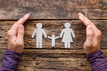 Man takes care of family - concept on wooden background