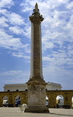 Sanctuary of St. Mary of Leuca. The lighthouse is partially covered by the statue of the Madonna on a high column. Apulia - Italy