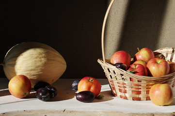 A full wicker basket of apples and fresh prunes, lying submerged fragrant melon