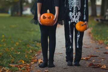Body shots of boy and girl in skeleton outfits holding pumpkins