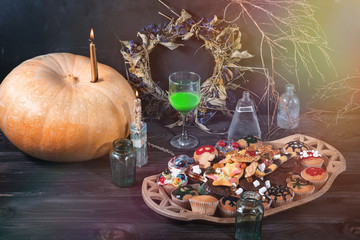 Pumpkin, candle, green liquid in a glass, sweets, cookies, jars, dry twigs and leaves on a table
