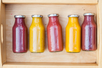 Blend or crushed fruit juice or smoothie in wooden box on old rustic wooden table, top view, selective focus. Detox, dieting, clean eating, vegetarian, vegan, fitness, healthy lifestyle concept