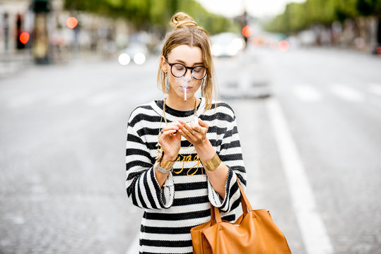 Young stylish woman in striped sweater with eyeglasses smoking a cigarette standing outdoors on the street in Paris