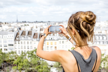 Young woman tourist photographing with phone beautiful skyline in Paris