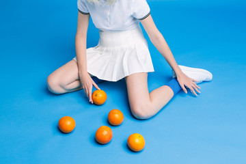 Woman in white dress posing with ripe oranges