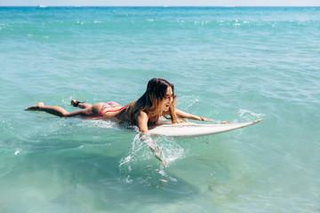 Pretty funny brunette swims on surf in ocean