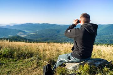 Fototapeta Mężczyzna robi zdjęcia telefonem komórkowym w górach. obraz