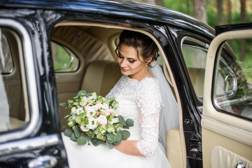 Handsome gorgeous bride in white wedding dress with bridal bouquet in the old car