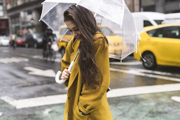 Young woman walking under the rain in New York City