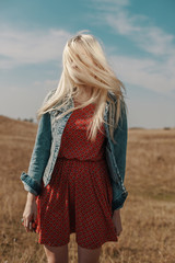 Blond woman on a yellow grass field