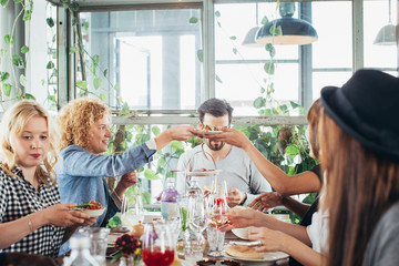 Group of Five Caucasian Friends Eating Lunch in Stylish Bright Restaurant