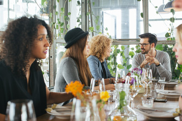 Group of Five Friends Eating Out in Stylish Restaurant