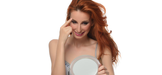 portrait of a beautiful young woman with elegant long red shiny hair touching her face in front of mirror