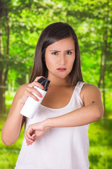 Beautiful young woman using a spay over the insect to kill it, in a blurred background