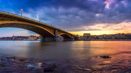Budapest, Hungary - Panoramic shot of the Beautiful colorful sunset and clouds at the Margaret Bridge taken from Margaret Island at dusk