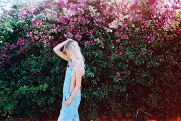 A blonde girl in overalls against pink flower wall