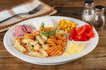 Salad of pasta fusilli with tomatoes corn cheese and ham on wooden background