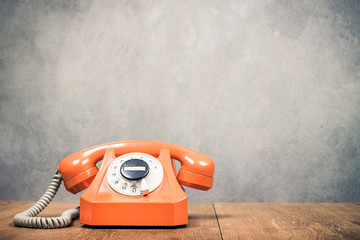 Old orange retro rotary telephone on table front textured concrete wall background. Vintage style filtered photo