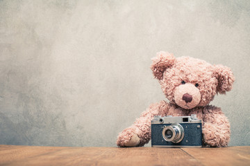 Retro Teddy Bear toy sitting at the wooden desk with old outdated rangefinder film camera from 50s front concrete wall texture background. Vintage style filtered photo