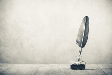 Quill pen with inkwell  on wooden desk. Vintage old style sepia photography