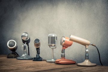 Retro old microphones for press conference or interview on the desk. Vintage style filtered photo