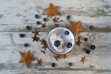 Blueberry smoothie drink in rustic setting with stars top view