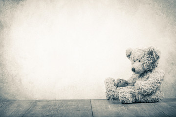 Retro Teddy Bear toy sitting alone abandoned front old textured concrete wall background. Vintage style sepia photo