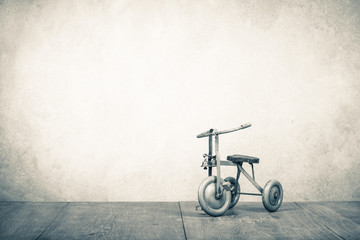 Old retro toy bicycle with three wheels. Vintage style sepia photo