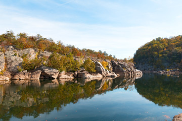 A scenic river bend in Great Falls park, Virginia, USA. Mountainous banks of Potomac River with trees in autumn foliage.