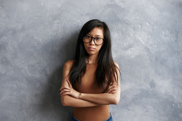 Portrait of offended stubborn young brunette Asian woman wearing eyeglasses standing isolated at grey textured wall, keeping arms folded, looking at camera with angry expression on her face