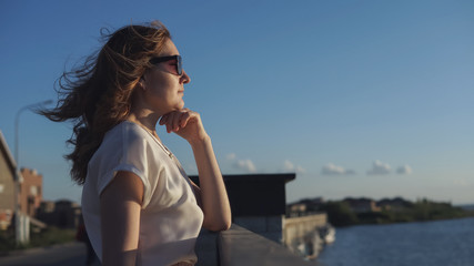 Beautiful girl enjoys the sunset on the waterfront