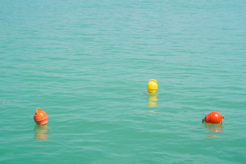 Three bright yellow and orange marker buoys floating in blue turquoise lake water, Balaton, Hungary. Abstract composition of water safety.