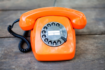 Retro phone orange color, handset receiver on wooden textured background. Shallow depth field photography.