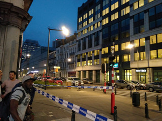 People walk next to the scene where a man attacked two soldiers with a knife in Brussels, Belgium August 25, 2017 in this picture obtained from social media