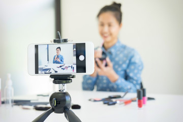 woman present beauty product and broadcast live video to social network by internet at home, beauty blogger concept.