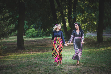 couple of boho style women run barefoot through the park