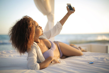Girl making a selfie, lying down on a bed at the beach
