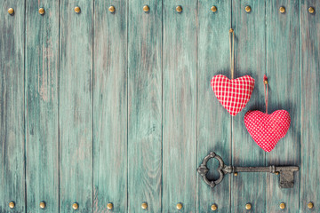 Pair of love hearts and old rusty key on wooden vintage background. Retro style filtered photo
