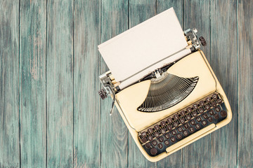 Retro old portable compact typewriter from 70th with paper sheet on mint green wooden table. Vintage style filtered photo