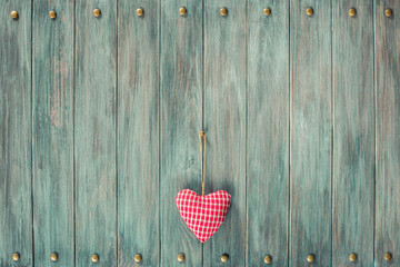 Valentine love heart on vintage old grunge textured planks wall background. Retro style filtered photo