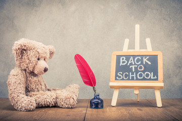 Retro Teddy Bear toy, red quill pen in the inkwell and Back to School written on a blackboard front concrete wall background. Vintage style filtered photo
