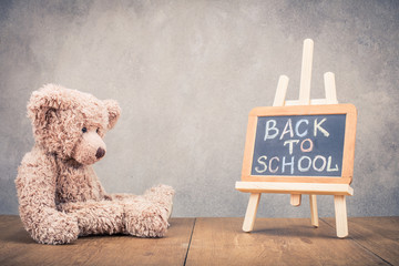 Retro Teddy Bear toy and Back to School written on a blackboard front concrete wall background. Vintage instagram style filtered photo