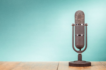 Retro big microphone from 50s on table front gradient mint green background. Vintage old style filtered photo