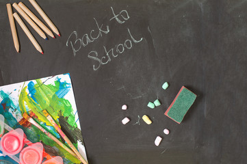 Back to school composition and a writing on a black chalkboard background. Top view to items: color pencils, chalk, paint brushes.