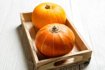 Halloween pumpkins on wooden tray