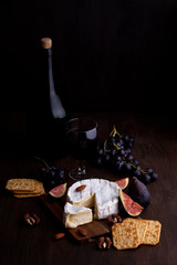 French cheese camembert with glass of red wine, grapes and figs