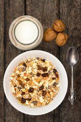 White bowl with Granola or Muesli and a jar of milk or plain yogurt with a spoon on a vintage wood background. Healthy breakfast top view composition