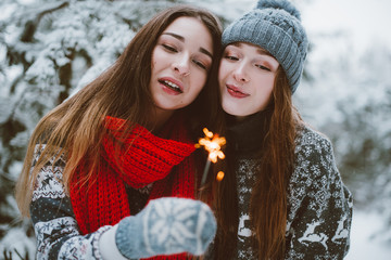 Close up fashion portrait of two sisters hugs and having fun, drinking tea winter time,wearing red santa hats and sweater,best friends couple
