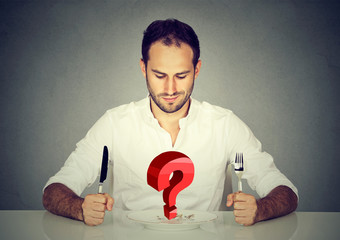 Man with fork and knife sitting at table looking at plate with big red question
